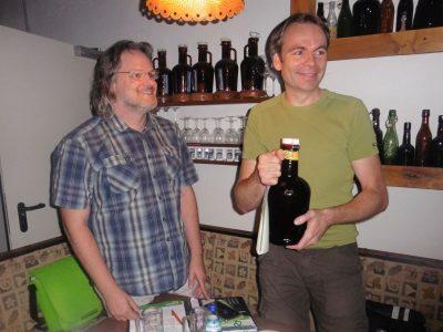 John Haberle (r.), Sprecher des GRÜNEN Kreisverbandes Mark mit einer Flasche Rönsahler Bier, überreicht von Detlef Jungmann (l.), Sprecher des GRÜNEN Ortsverbandes Kierspe.